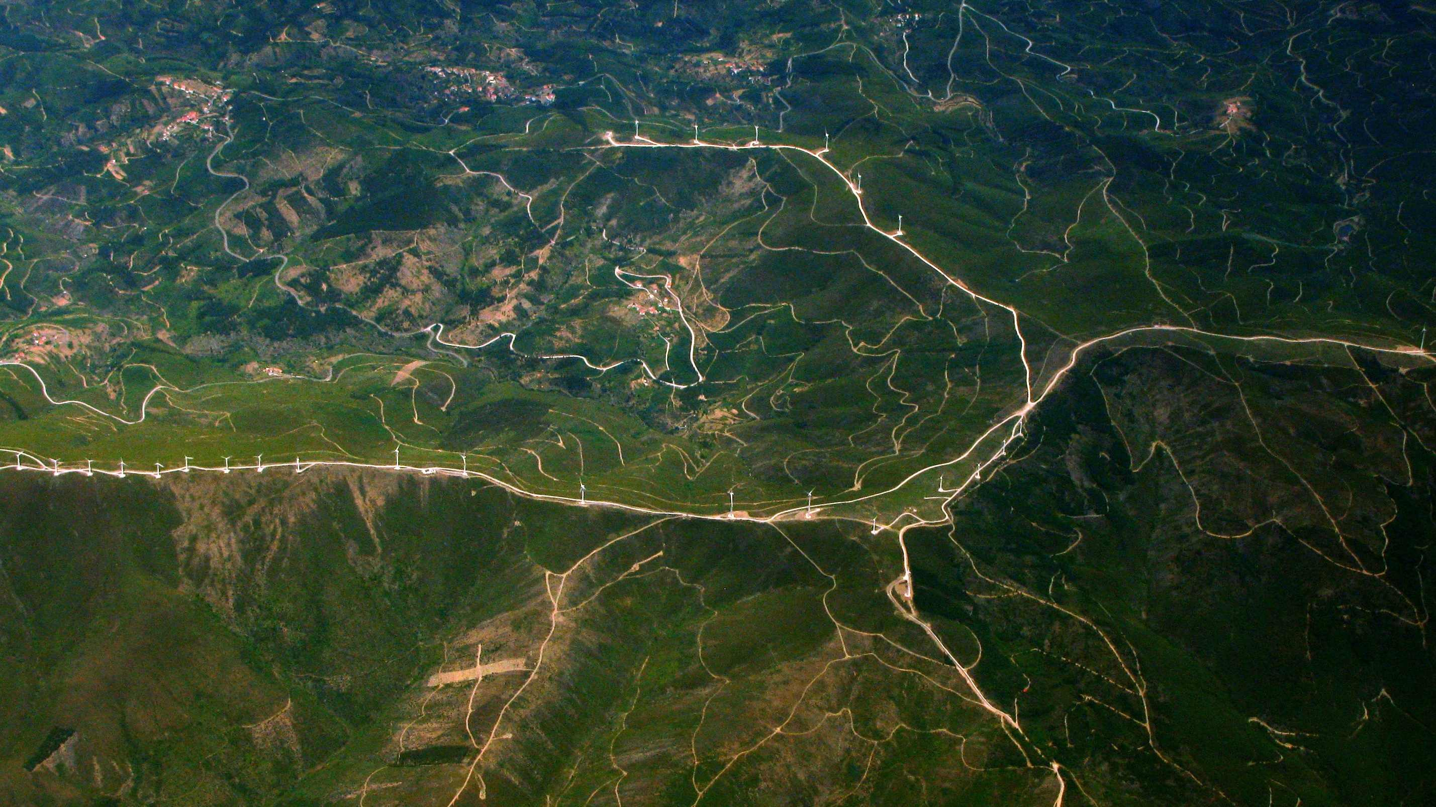 An aerial view of roads stretching across green hills
