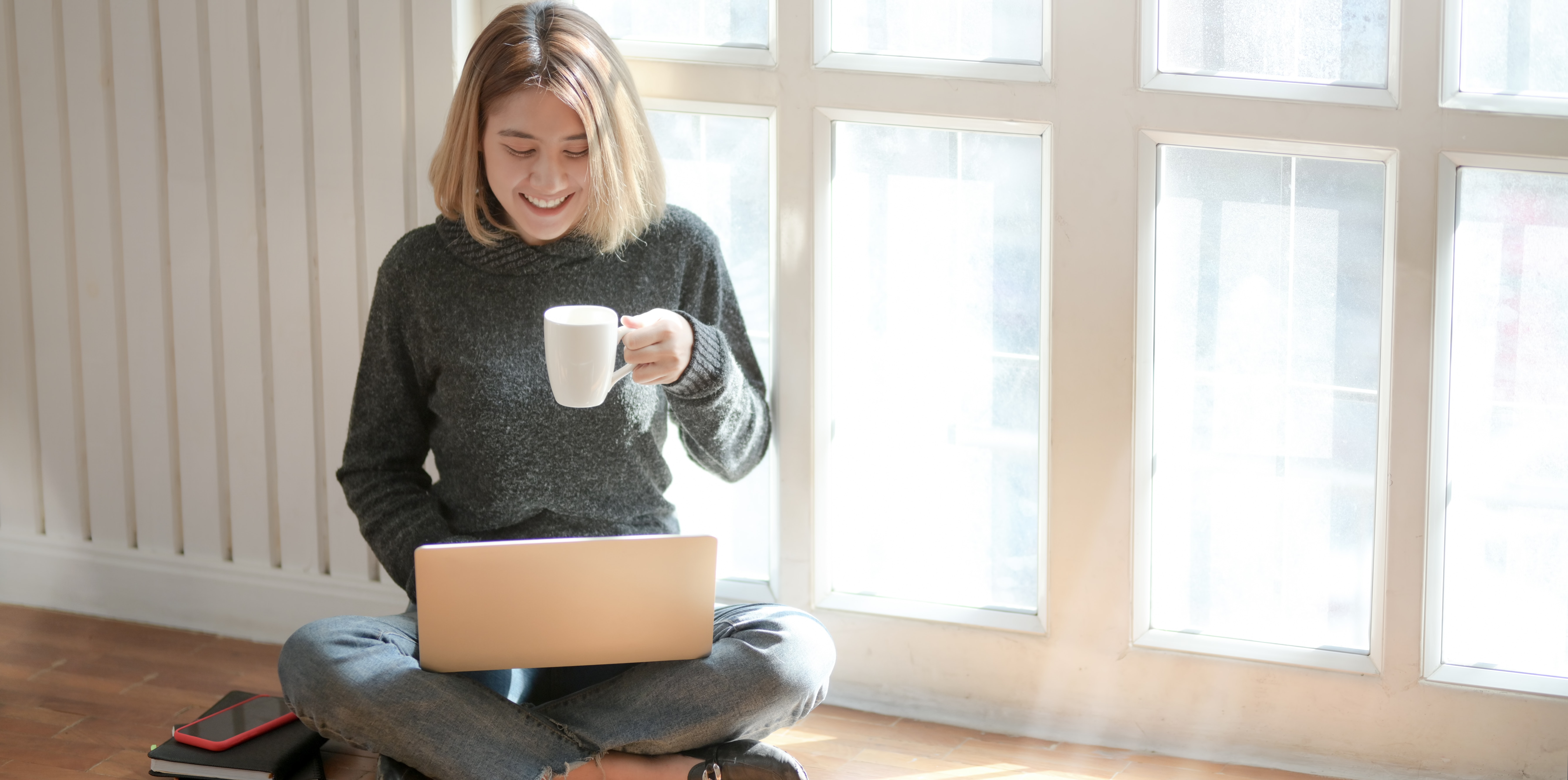 Woman in gray sweater drinking coffee on laptop