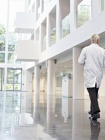 Two men in lab coats walking through a foyer