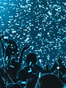 Image of people celebrating under confetti in blue
